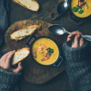 Woman in a knitted jumper eating pumpkin soup