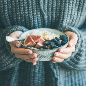 Woman in a knitted jumper holding a bowl of healthy food