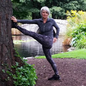 Kim Stansfield doing yoga on a tree in a park