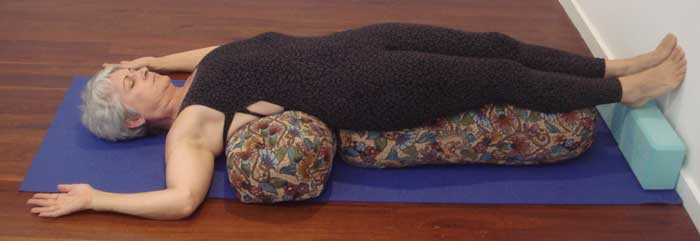 Kim Stansfield doing a restorative pose with mild back bend