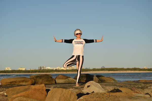 Kim Stansfield doing tree yoga pose on rocks