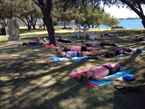 Group doing yoga relaxing at the park Gold Coast Broadwater Southport