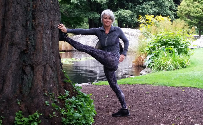 Kim Stansfield doing a hamstring stretch against a tree in a park