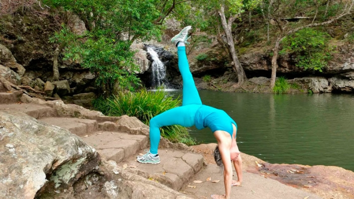 Kim Stansfield doing a wheel pose in turquoise outfit in front of a water fall