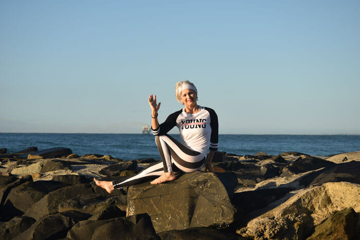 Kim Stansfield waving on rocks at the beach at caloundra
