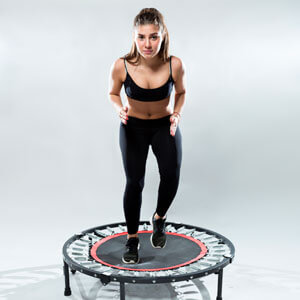 A young teenage woman jumping on a rebounder